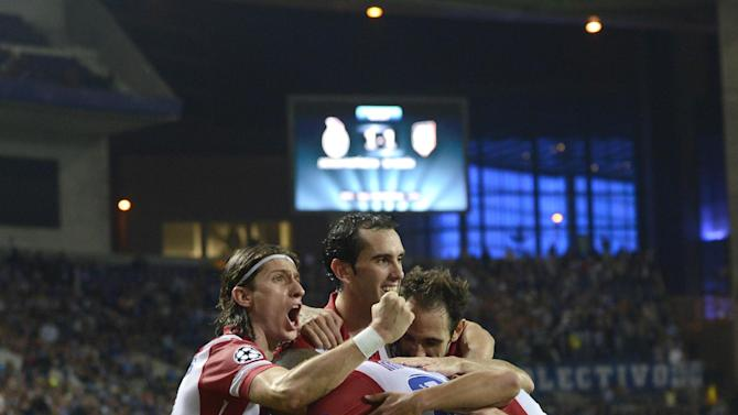 Atletico's Arda Turan, left on the pitch, celebrates with teammates after scoring his side's second goal during the Champions League group G soccer match between FC Porto and Atletico de Madrid Tuesday, Oct. 1, 2013, at the Dragao stadium in Porto, northern Portugal. Atletico won 2-1