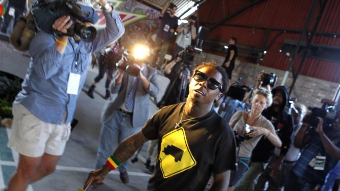 Recording artist Lil Wayne carries a skateboard at a new park he helped finance along with Glu Agency and Mountain Dew, in the Lower Ninth Ward of New Orleans, Wednesday, Sept. 26, 2012. (AP Photo/Gerald Herbert)