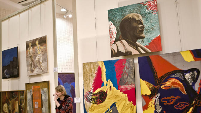 A picture taken Thursday, Sept. 27, 2012, shows a man visiting an exhibition of visual art created by Romanian artists during the Communist period, between 1950 and 1990, in Bucharest, Romania. Opposed to the typical works used as a propaganda tool to glorify late Communist dictator Nicolae Ceausescu, the new exhibit of some 650 paintings, unveiled Thursday evening at the National Library, seeks to show that painters were not solely guided by politics, in an effort to restore pride in the nation's cultural heritage.(AP Photo/Vadim Ghirda)