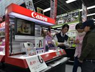 Shares in Canon fell on Thursday, helping to keep Tokyo's Nikkei index flat as Asian markets mostly edged up after a cautiously upbeat assessment of the US economy by the Federal Reserve and comments from its chairman that he would provide more support if necessary