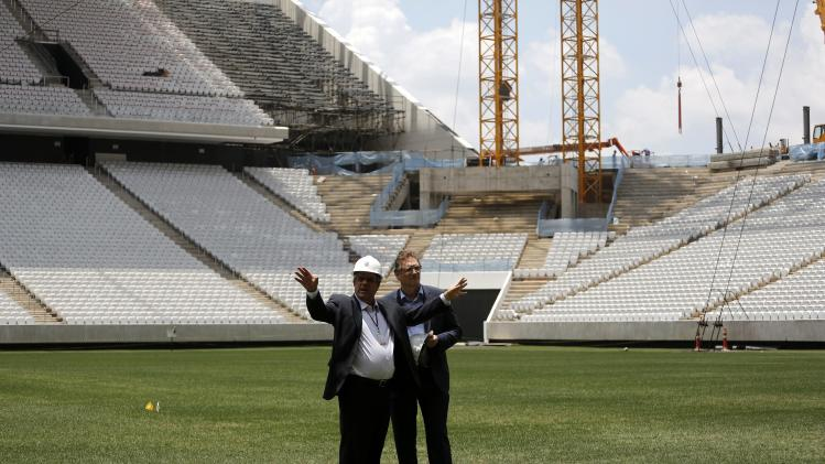 FIFA Secretary General Valcke talks with an engineer during a visit to the site of the Arena Corinthians stadium, which is being prepared to host 2014 World Cup matches, in Sao Paulo
