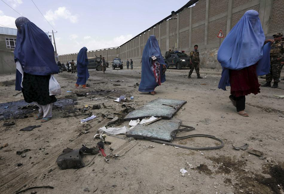 Afghan women walk after a car bomb attack in Kabul