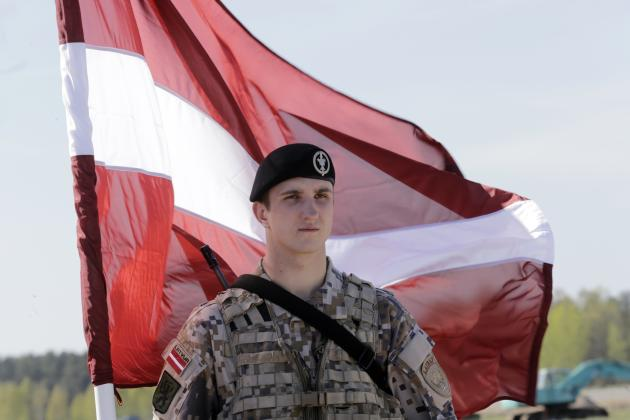 A Latvian soldier holds a national flag as he waits for about 150 U.S. paratroopers from the U.S. Army's 173rd Infantry Brigade Combat Team based in Italy to arrive in the airport in Riga