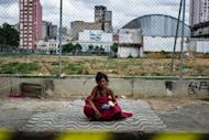 """A 40-year old homeless woman sits after receiving food provided by NGOs and social groups during their demonstration against military police's clean-up operation in the area called """"Cracolandia (Crackland in English)"""" in downtown of Sao Paulo, Brazil, on January 14"""