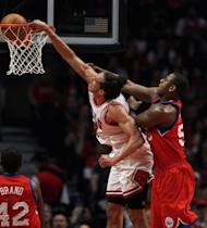 Joakim Noah of the Chicago Bulls dunks the ball over Elton Brand (L) and Lavoy Allen (R) of the Philadelphia 76ers in Game One of the Eastern Conference quarter-finals during the 2012 NBA Playoffs at the United Center in Chicago, Illinois. Chicago won 103-91