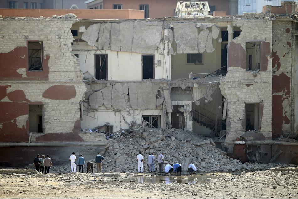 Egyptian security officials inspect the site following a bomb blast at the Italian Consulate in Cairo