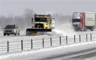 A snow plow clears the road on Interstate 65 north of Indianapolis, Indiana January 6, 2014. REUTERS/Nate Chute