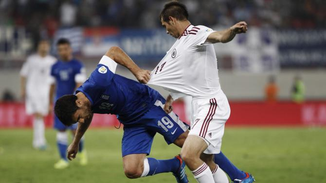 Greece's Papastathopoulos challenges Latvia's Zjuzins during their 2014 World Cup qualifying soccer match in Piraeus near Athens