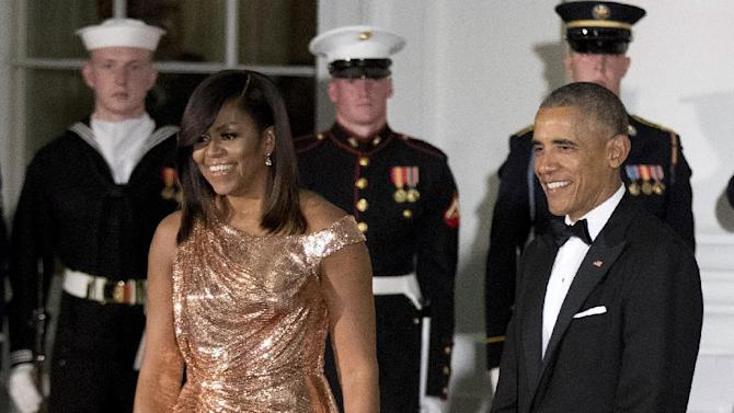 President Barack Obama and first lady Michelle Obama wait at North Portico of the White House to greet Italian Prime Minister Matteo Renzi and his wife Agnese Landini, for a State Dinner, Tuesday, Oct. 18, 2016. The first lady is wearing a floor length, rose gold chainmail gown designed by Atelier Versace. (AP Photo/Manuel Balce Ceneta)