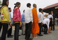 Cambodian students and a Cambodian Buddhist monks, center, line up in front the court of the U.N.-backed war crimes tribunal during the second trial to the top leaders of Khmer Rouge, on the outskirts of Phnom Penh, Cambodia, Thursday, June 30, 2011. The tribunal on Thursday held its fourth day trial on top four surviving members of the Khmer Rouge regime, blamed for the deaths of an estimated 1.7 million Cambodians in the 1970s. (AP Photo/Heng Sinith)