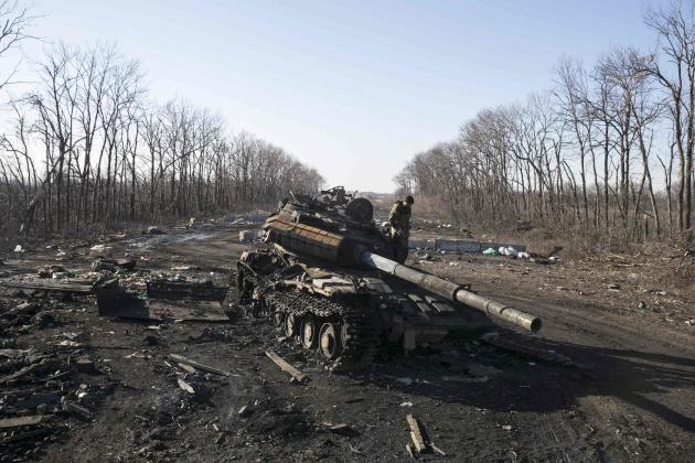 Fighter with the separatist self-proclaimed Donetsk People's Republic army looks at a destroyed Ukrainian army tank near the town of Debaltseve