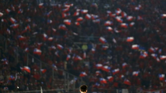 Argentina's Lionel Messi stands on the pitch with a sea of Chile flags held by fans in the background during their Copa America 2015 final soccer match at the National Stadium in Santiago