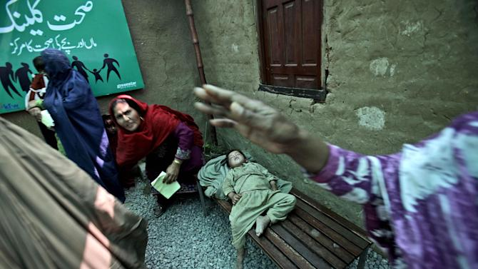 In this Wednesday, April 18, 2012, photo, an Afghan refugee boy, center, sleeps on a bench, while his mother waits her turn to receive free medicine from a clinic, in a slum on the outskirts of Islamabad, Pakistan. Hundreds of thousands of Afghan refugees are in limbo as Pakistan, increasingly frustrated with hosting the world's largest and longest-running refugee population, weighs whether to renew their refugee status by the end of this year. A large-scale return of the 1.7 million Afghan refugees currently living in Pakistan would be a massive problem for Afghanistan at a time when it's already struggling to maintain security in the face of an American troop withdrawal. But Pakistan increasingly seems to be angry at a refugee population that many feel has overstayed its welcome. (AP Photo/Muhammed Muheisen)