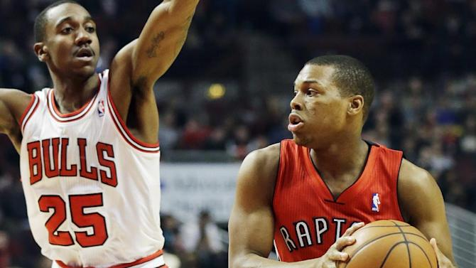 Toronto Raptors guard Kyle Lowry, right, looks to a pass as Chicago Bulls guard Marquis Teague guards during the first half of an NBA basketball game in Chicago on Saturday, Dec. 14, 2013