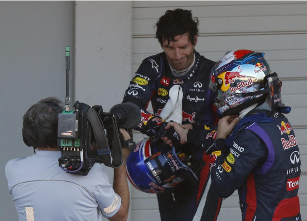 Second-placed Red Bull Formula One driver Webber of Australia shakes hands with Red Bull Formula One driver Vettel of Germany after Vettel won the Japanese F1 Grand Prix at the Suzuka circuit