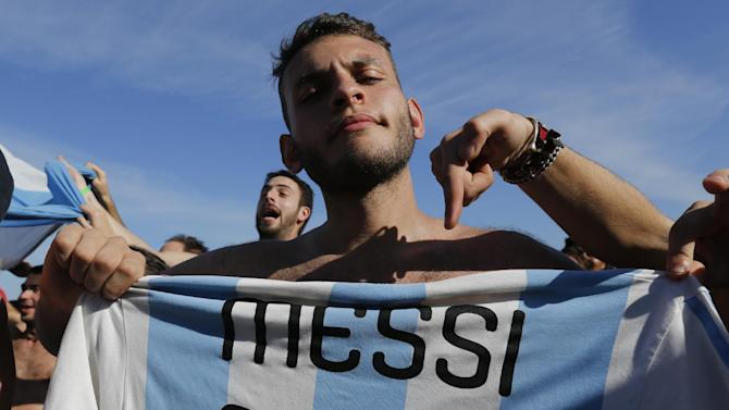 A soccer fan of the Argentina national soccer team poses with a Messi soccer jersey on Copacabana beach, in Rio de Janeiro, Brazil, Saturday, July 5, 2014. Argentina defeated Belgium 1-0 to reach the World Cup semifinals for the first time since 1990