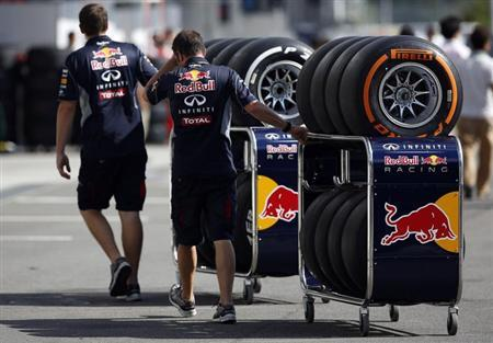 Red Bull Formula One team members move Pirelli tires near the pits at the Suzuka circuit in Suzuka October 10, 2013, ahead of Sunday's Japanese F1 Grand Prix. REUTERS/Issei Kato
