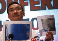 Malaysia's acting Transport Minister Hishamuddin Hussein shows maps of southern corridor and northern corridor of the search and rescue operation during a press conference at a hotel near the Kuala Lumpur International Airport, in Sepang, Malaysia, Monday, March 17, 2014. Twenty-six countries are involved in the massive international search for the Malaysia Airlines jetliner that disappeared on March 8 with 239 people aboard. They include not just military assets on land, at sea and in the air, but also investigators and the specific support and assistance requested by Malaysia, such as radar and satellite information. (AP Photo/Vincent Thian)