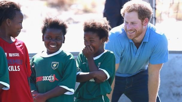 Prince Harry laughs with young girls during a visit to a Football for Hope session with Grassroots Soccer in Khayelitsha, Nov. 30, 2015,in Cape Town, ...