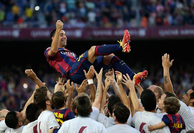 FILE - In this May 23, 2015 file photo FC Barcelona's Xavi Hernandez is thrown into the air by his teammates after winning the Spanish League title, at the end of their Spanish La Liga last round