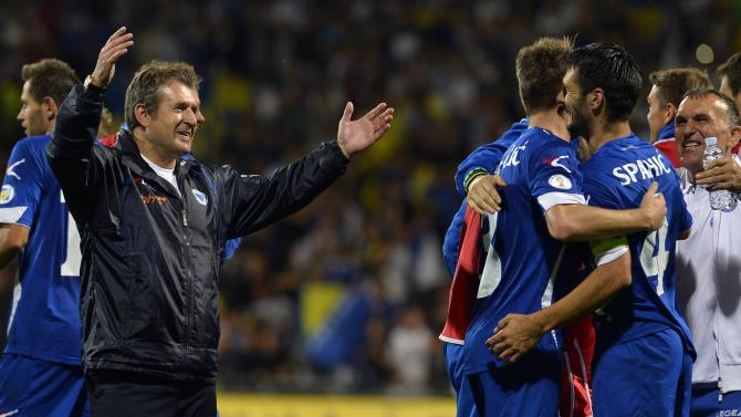 Bosnia's Emir Spahic celebrates with his team and head coach Safet Susic after their 2014 World Cup qualifying soccer match against Slovakia in Zilina
