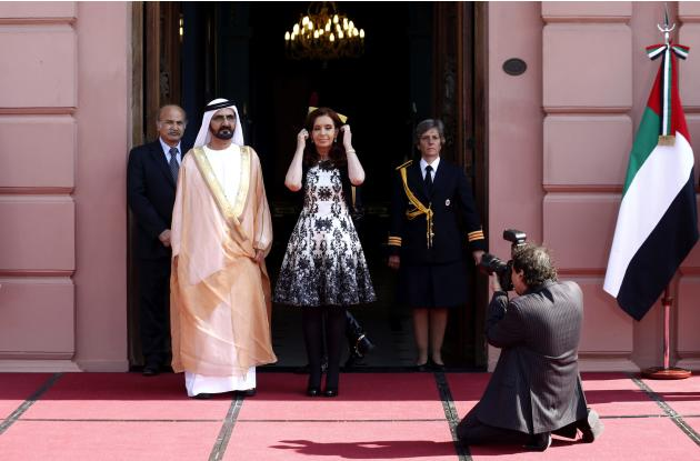 Argentina's President Fernandez de Kirchner arranges her hair as she poses next to Sheikh Mohammed Bin Rashid Al Maktoum, Vice President and Prime Minister of the United Arab Emirates, in Buenos A