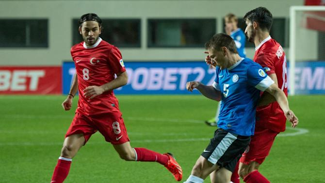 Estonia's Dmitri Kruglov, right front,  fights for the ball with Turkey's Mehmet Topal and  Selcuk Inan, left, during their World Cup Group D qualifying soccer match in Tallinn, Estonia, Friday, Oct. 11, 2013