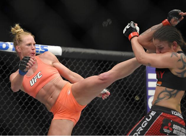 Holly Holm, left, connects with Raquel Pennington during a UFC 184 mixed martial arts bantamweight bout, Saturday, Feb. 28, 2015, in Los Angeles. Holm won by a split decision. (AP Photo/Mark J. Terril