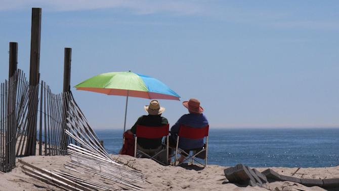 Daryl Gottilla, left, and his wife Denise, right, sit on a storm-damaged beach in Point Pleasant Beach NJ on May 10, 2013. Visitors to the Jersey shore this Memorial Day weekend will find many of their favorite beaches and boardwalks ready for summer, thanks to a massive rebuilding effort after Superstorm Sandy. While several neighborhoods remain damaged, all but one of the storm-wrecked boardwalks should be ready for Memorial Day weekend, and amusement rides will still be available from Keansburg to Wildwood. Most beaches will be open, despite losing sand during the storm. (AP Photo/Wayne Parry)