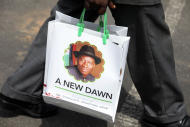 A man carries a bag with the portrait of Nigerian President Goodluck Jonathan during his inauguration ceremony at the main parade ground in Nigeria's capital of Abuja Sunday, May 29, 2011. Goodluck Jonathan was sworn in Sunday for a full four-year term as president of Nigeria and is now faced with the challenge of uniting a country that saw deadly postelection violence despite what observers called the fairest vote in over a decade.