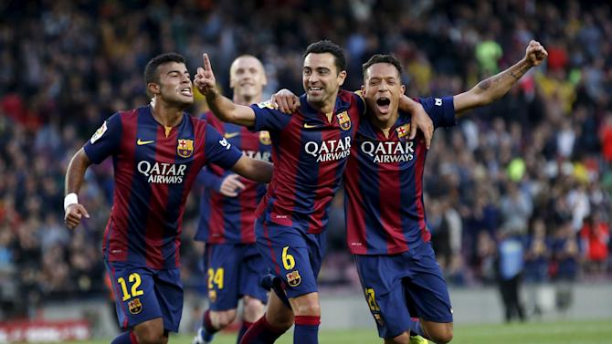 Barcelona's Xavi Hernandez celebrates his goal against Getafe with teammates Rafinha and Adriano during their Spanish first division soccer match at Nou Camp stadium in Barcelona