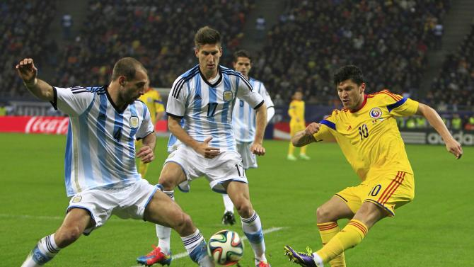 Romania's Tanase challenges Argentina's Zabaleta and Fernandez during their international friendly soccer match at the National Arena in Bucharest