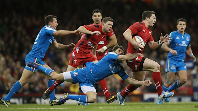 Wales's George North, second right is tackled by Italy's Angelo Esposito, center, during their Six Nations international rugby union match between Wales and Italy at the Millennium stadium in Cardiff, Wales, Saturday, Feb. 1, 2014 (AP Photo/Alastair Grant)