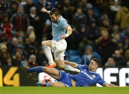 Manchester City's Alvaro Negredo (L) is challenged by Chelsea's Gary Cahill during their English FA Cup fifth round soccer match at the Etihad Stadium in Manchester, northern England February 15, 2014. REUTERS/Nigel Roddis