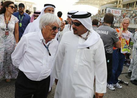 Bahrain's Crown Prince Salman bin Hamad al-Khalifa speaks with Formula One's commercial supremo Ecclestone as they arrive before the Bahrain F1 Grand Prix at the Sakhir circuit