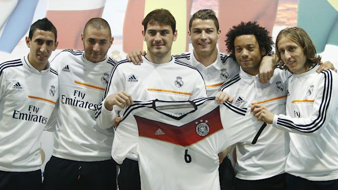 Real Madrid's Cristiano Ronaldo from Portugal centre right, Iker Casillas, centre left, Angel Di Maria from Argentina, left, Karim Benzema from France, second left, Marcelo from Brazil, second right, and Luka  Modric from Croatia, right, pose with Germany's Sami Khedira national t-shirt during a press conference on the 2014 soccer World Cup in Madrid, Spain, Sunday, Dec. 8, 2013