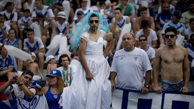 A Velez Sarsfield fan wearing a bride's dress stands before the start of the final match of Argentina soccer league championship against San Lorenzo in Buenos Aires, Argentina, Sunday, Dec. 15, 2013