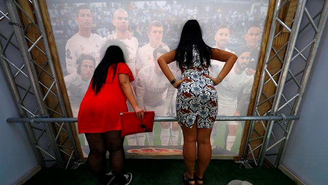 Fans pose for a photograph behind the Real Madrid team poster near Duomo's square prior to the UEFA Champions League Final in Milan