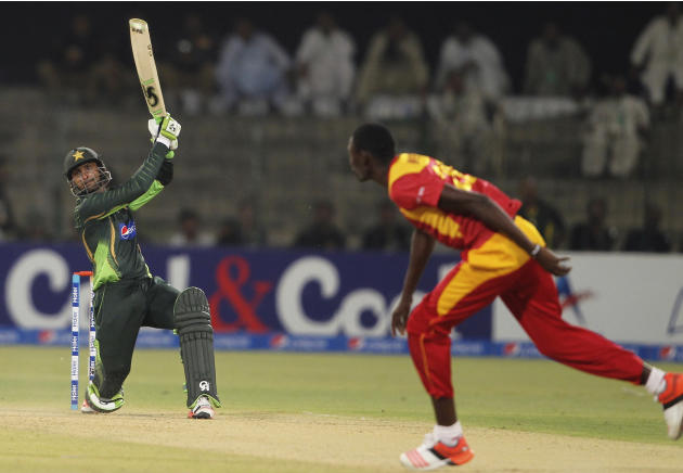 Pakistan's Shoaib Malik hits boundary as Zimbabwe's Christopher Mpofu looks on during a one-day international match at the Gaddafi Stadium in Lahore, Pakistan, Tuesday, May 26, 2015. Malik mad