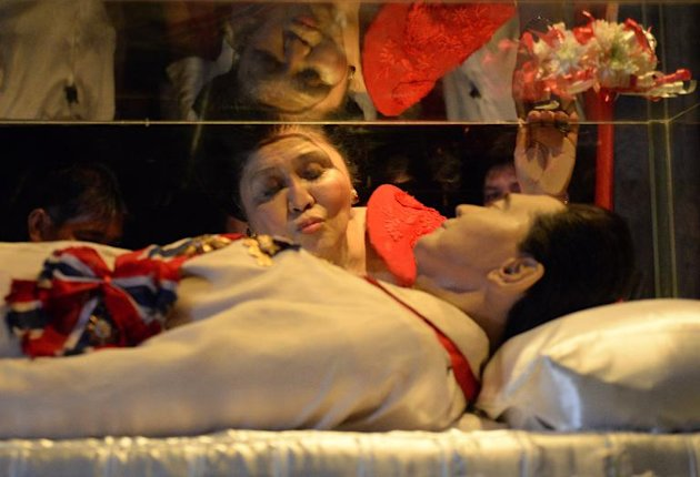 Former Philippine first lady Imelda Marcos kisses the glass case of her late husband, president Ferdinand Marcos, in Batac town north of Manila, July 2, 2014