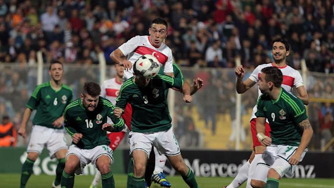 Turkey's Mevlut Erdinc, top-rear, and Daniel Lafferty of Northern Ireland, center-front, in action during their friendly soccer match in Adana, Turkey, Friday, Nov. 15, 2013.(AP Photo)