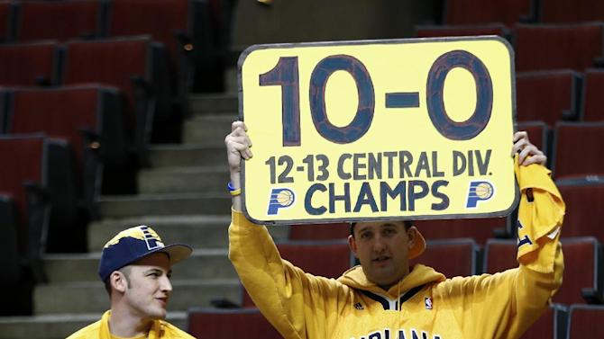 An Indiana Pacers fan hoists up a placard in support of his team before the Pacers' NBA basketball game against the Chicago Bulls in Chicago, Saturday, Nov. 16, 2013