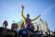 Bradley Wiggins, winner of the 2012 Tour de France, celebrates with his teammates during a parade on the Champs-Elysees Avenue on July 22. Wiggins' victory elevates him to the pantheon of British sporting greats and should see him receive a knighthood, Britain's press said on Monday