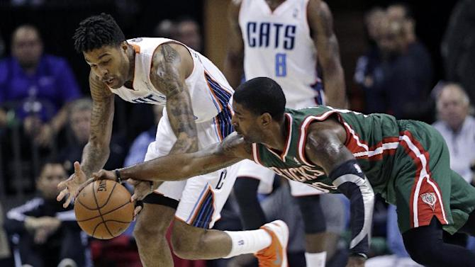 Milwaukee Bucks' O.J. Mayo, right, and Charlotte Bobcats' Chris Douglas-Roberts, left, chase the loose ball during the first half of an NBA basketball game, Monday, Dec. 23, 2013, in Charlotte, N.C