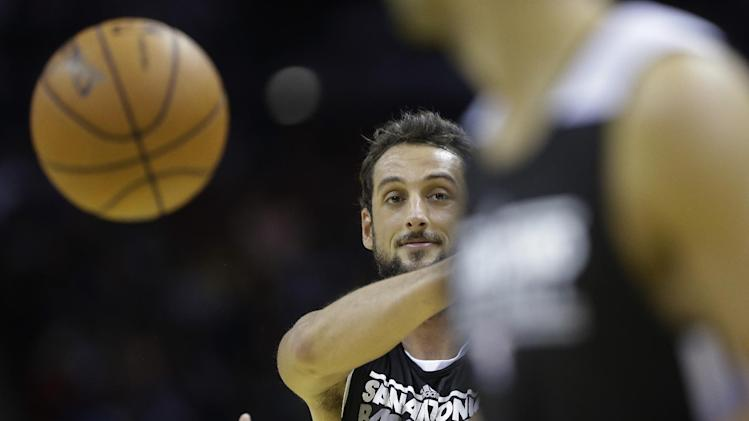 San Antonio Spurs' Marco Belinelli, left, of Italy, passes the ball during an open NBA basketball practice on Sunday, Oct. 6, 2013, in San Antonio