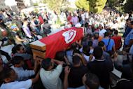 Tunisians carry the coffin of one of the six policemen that were killed in a firefight with suspected jihadists, Socrate Cherni, on October 24, 2013 before his burial at Ben Anin cemetery in Kef
