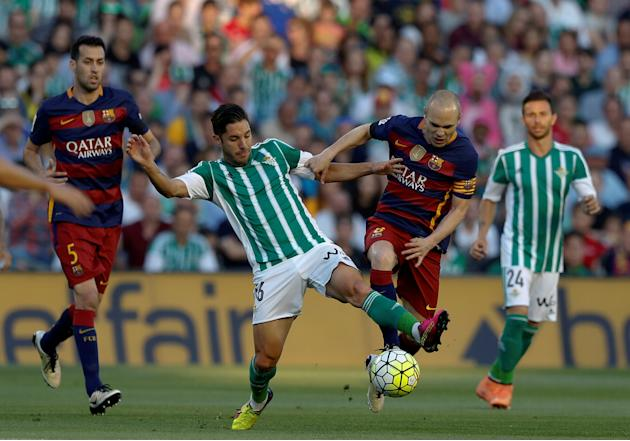 Barcelona's Andres Iniesta and Real BetisÕ Alvaro Cejudo in action
