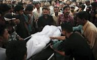 Pakistani relatives carry the body of a garment factory fire victim during a funeral in Karachi