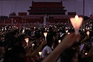 Protestors hold up candles in front of a large poster of Tiananmen Square during a candlelight vigil in Victoria Park in Hong Kong. Hong Kong held a candlelight vigil Monday to mark the 23rd anniversary of the Tiananmen Square crackdown, in stark contrast to mainland China where activists said hundreds of people were detained