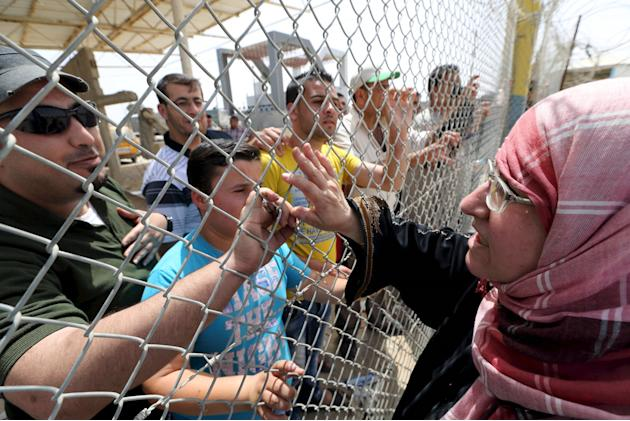 Palestinian woman waves to her relatives standing behind a fence upon her return to Gaza through Rafah border crossing between Egypt and southern Gaza Strip
